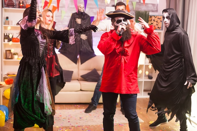 Mężczyzna w kostiumie pirata robi karaoke na imprezie halloweenowej z przyjaciółmi.