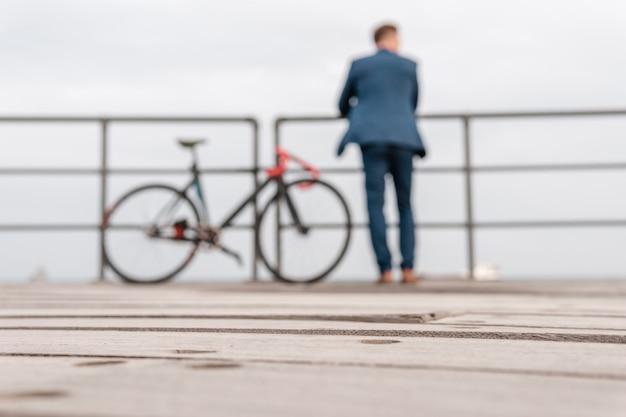 Mężczyzna w kostiumie stojący obok roweru