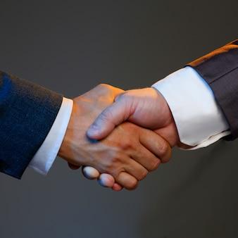 Mężczyzna w kostiumu trząść rękę jak cześć w biurowym zbliżeniu