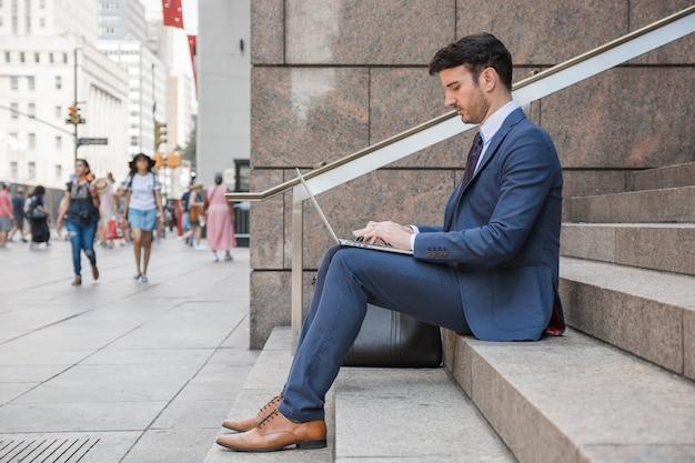 Mężczyzna w kostiumu używać laptop na ulicie