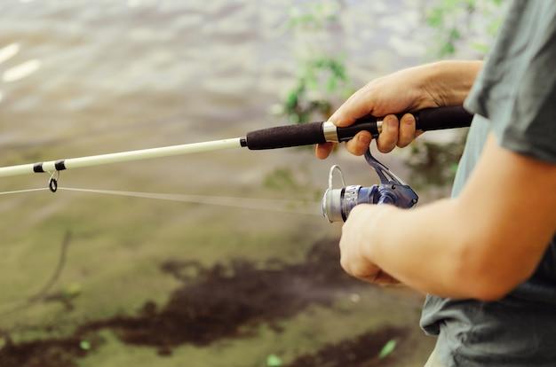 Mężczyzna w koszulce i ciemnych spodniach łowi ryby na jeziorze w letni dzień białą wędką z kołowrotkiem