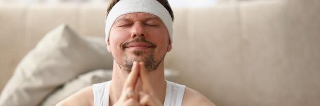 Mężczyzna w koszulce medytuje siedząc na podłodze w domu, po którym facet odpoczywa