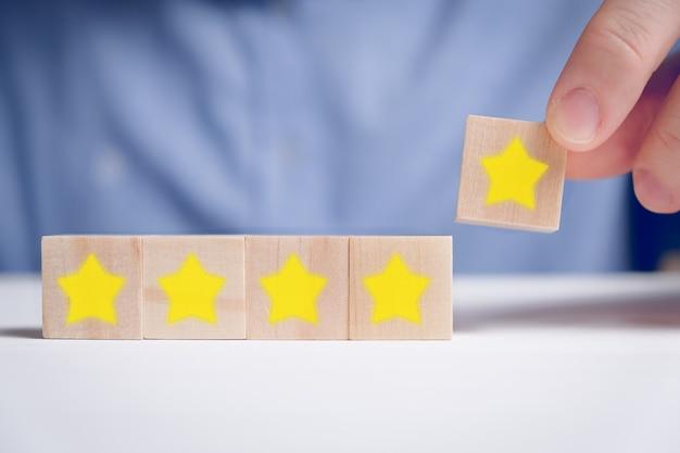 Mężczyzna w koszuli abstrakcyjnie oceniający pięć gwiazdek na drewnianych kostkach. najlepszy wynik