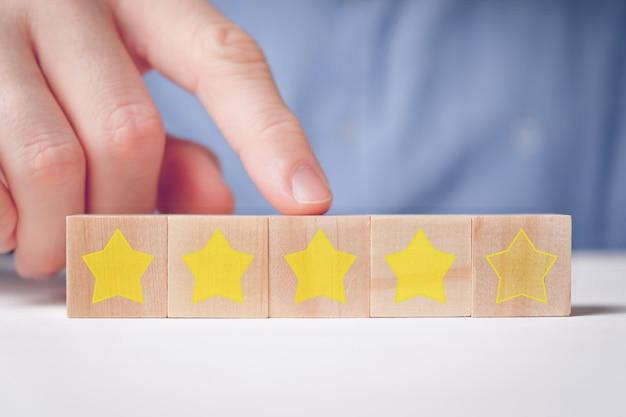 Mężczyzna w koszuli abstrakcyjnie pokazuje ocenę palcem z czterema gwiazdkami na drewnianych kostkach. dobra ocena