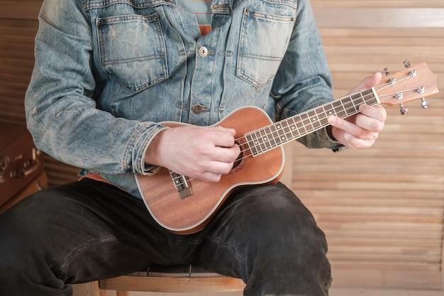 Mężczyzna w koszuli gra na ukulele