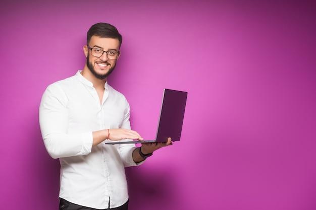 Mężczyzna w koszuli i krawacie trzymający laptopa i uśmiechający się stojąc na fioletowo
