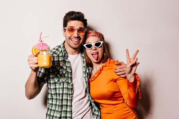 Mężczyzna w koszuli i okularach trzyma koktajl i przytula swoją ukochaną dziewczynę. kobieta w pomarańczowej sukience, chustce i okularach pokazuje język i znak pokoju.