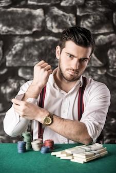 Mężczyzna w koszuli i szelkach siedzi przy stole pokerowym.