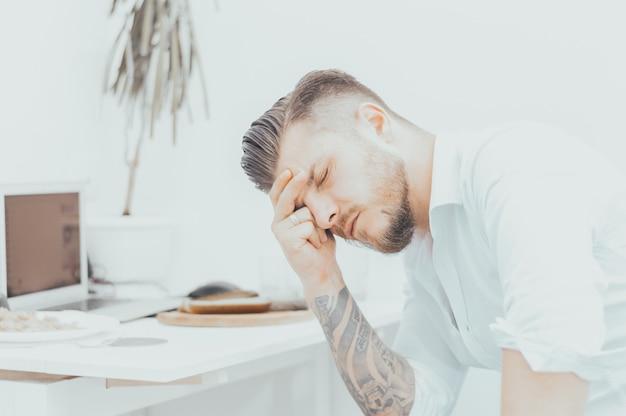 Mężczyzna w koszuli jest bardzo zdenerwowany nieprzyjemną wiadomością. zmęczony podparł głowę i zamknął oczy. pojęcie rozczarowania, porażki, straty. różne środki przekazu