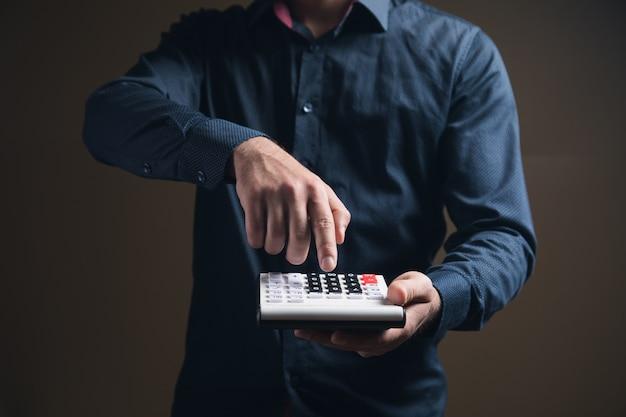 Mężczyzna w koszuli liczy na kalkulatorze na brązowej powierzchni