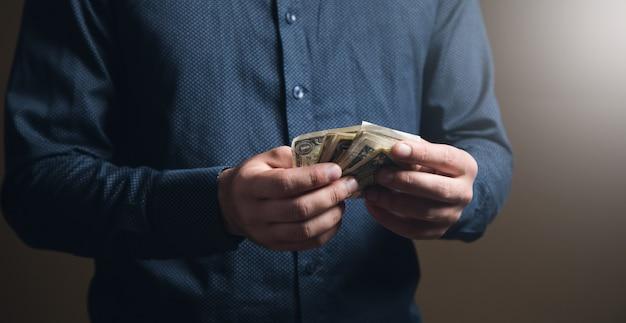Mężczyzna w koszuli liczy pieniądze na brązowej powierzchni