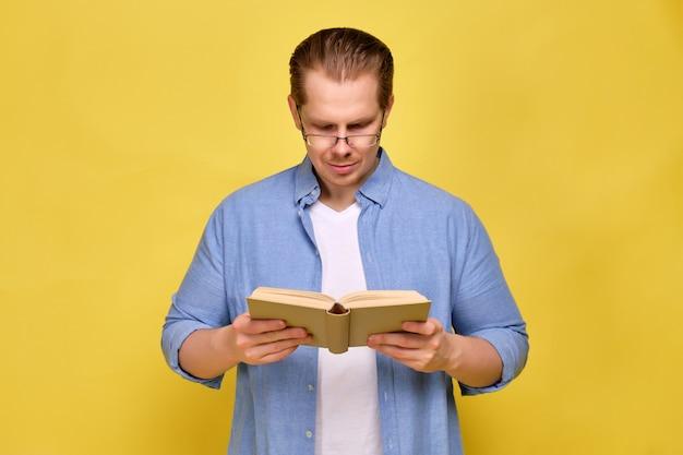 Mężczyzna w koszuli na żółto czyta książkę w okularach.