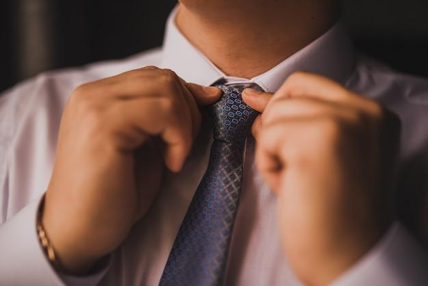 Mężczyzna w koszuli prostuje muszkę