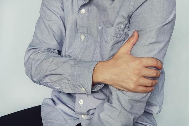 Mężczyzna w koszuli trzyma się barku, ręki, nadgarstka, przedramienia, kontuzji sportowej, odczuwania bólu, na niebieskim tle. ramienny. młody człowiek trzyma rękę pacjenta.
