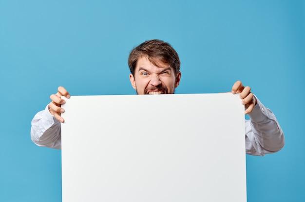 Mężczyzna w koszuli trzymając promocyjny billboard na niebieskim tle.