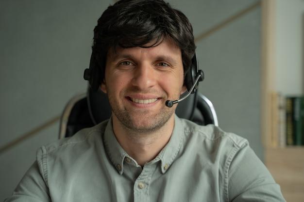 Mężczyzna w koszuli używa zestawu słuchawkowego w biurze mężczyzna patrzy i mówi do kamery siedząc przy biurku