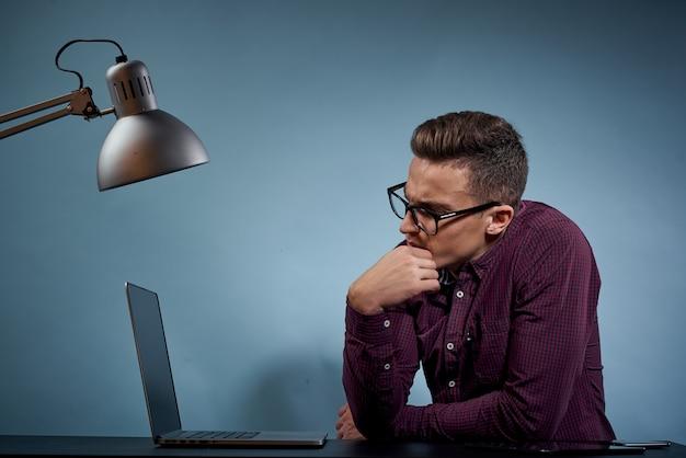 Mężczyzna w koszuli z laptopem przy stole to menadżer w biurze i model szafki na lampę