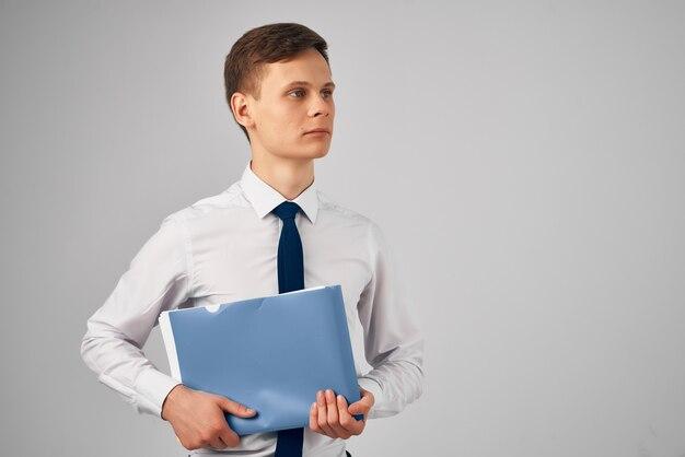 Mężczyzna w koszuli z niebieskim krawatem folderem w rękach szarym tle