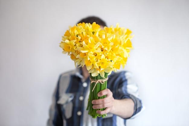Mężczyzna w koszuli zakrywa twarz bukietem kwiatów. pojęcie pozdrowienia i dzień kobiet.
