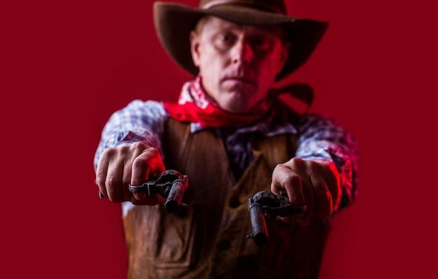 Mężczyzna w kowbojskim kapeluszu, pistolet. portret kowboja.