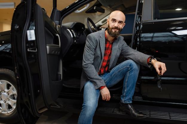 Mężczyzna w kowbojskim kapeluszu wybierając nowy samochód w salonie samochodowym. klient w salonie samochodowym, mężczyzna kupujący transport, firma dealera samochodowego dealer