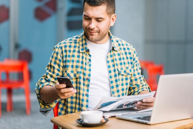 Mężczyzna w kraciaste koszule za pomocą telefonu