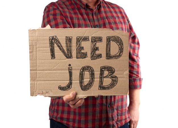 """Mężczyzna w kraciastej koszuli i dżinsach trzyma kartkę z napisem """"potrzebuję pracy"""""""