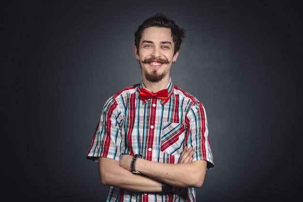 Mężczyzna w kraciastej koszuli i muszka w studio