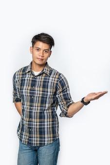 Mężczyzna w kraciastej koszuli otwiera dłoń po lewej stronie