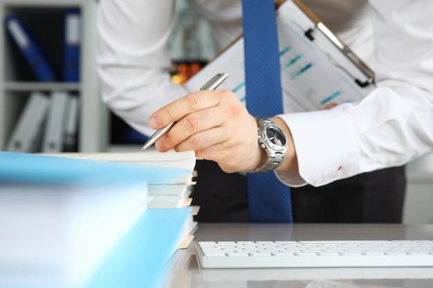 Mężczyzna w krawacie robi notatki na dokumentach na stole