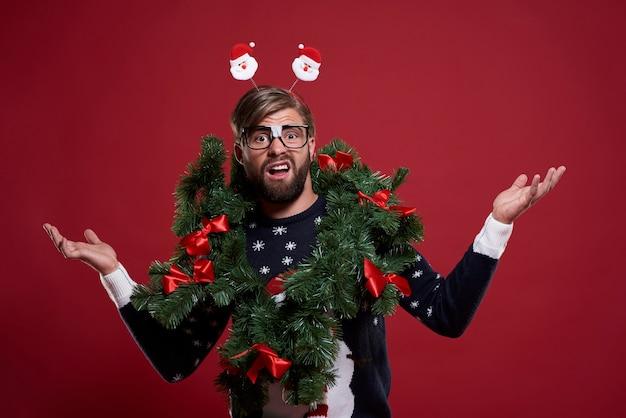 Mężczyzna w krępującej świątecznej girlandzie
