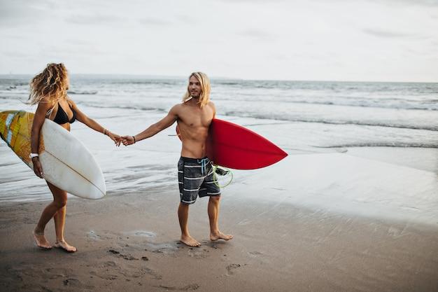 Mężczyzna w krótkich spodenkach i dziewczyna w stroju kąpielowym, trzymając się za ręce. para idzie surfować