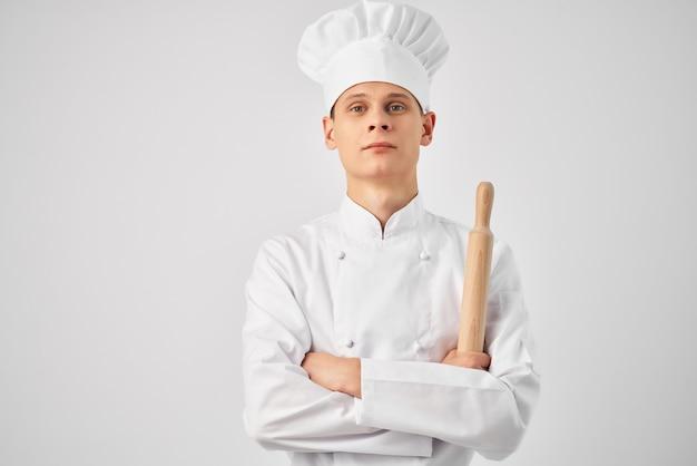 Mężczyzna w kucharskiej formie dzwonka w rękach profesjonalnego światła roboczego w tle