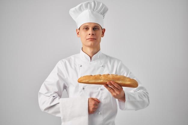 Mężczyzna w kucharzu umunduruje piekarza z bochenkiem w dłoniach świeżym produktem