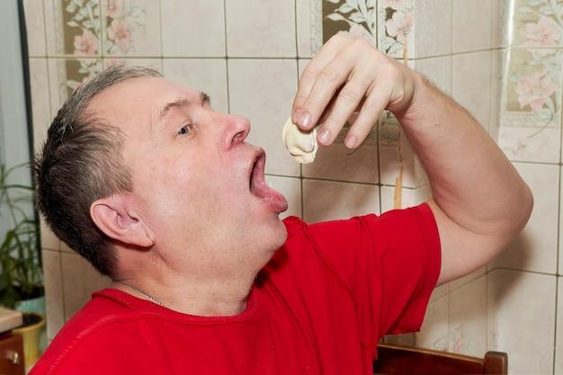 Mężczyzna w kuchni kładzie sobie kluskę z ręką w szeroko otwartych ustach