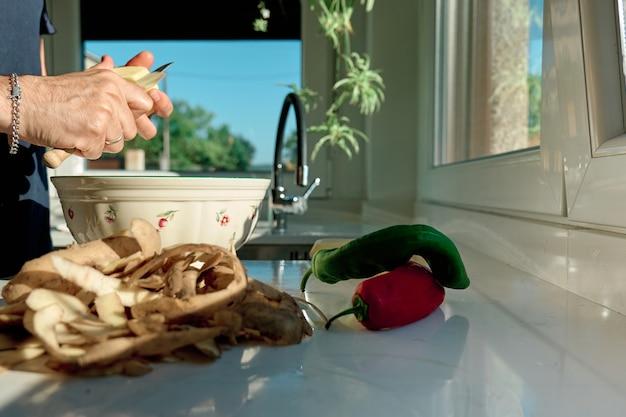 Mężczyzna w kuchni przygotowujący posiłek, obierający ziemniaki i warzywa, nie widać twarzy