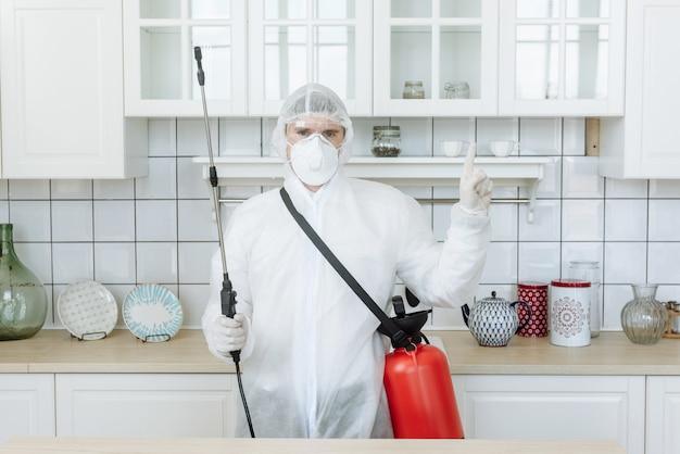 Mężczyzna w kuchni w kombinezonie ochronnym ze sprejem dezynfekującym do dezynfekcji artykułów gospodarstwa domowego i mebli koncepcja pandemicznej dezynfekcji koronawirusa lub covid