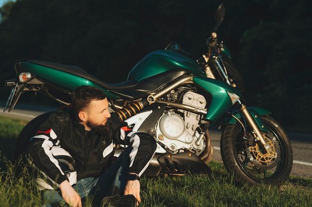 Mężczyzna w kurtce ochronnej siedzi na trawie, odpoczywając z kaskiem w ręku, opierając się na zielonym motocyklu stojącym na poboczu drogi w nocy, odwracając wzrok