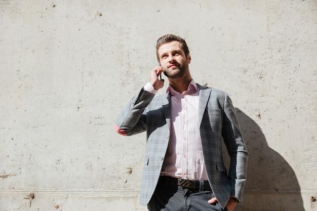 Mężczyzna w kurtce rozmawia przez telefon komórkowy i patrząc w górę