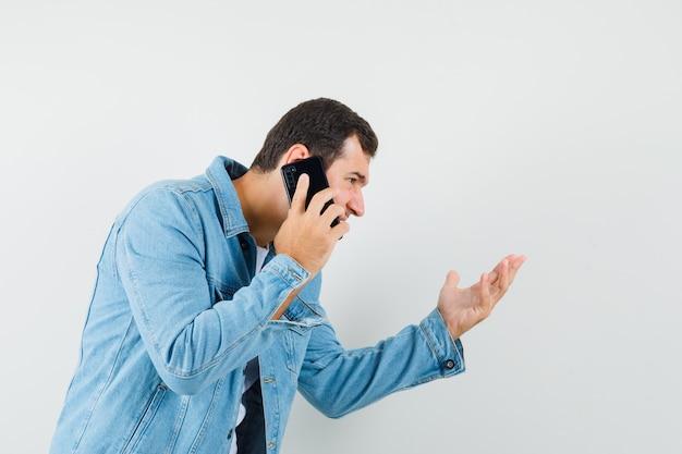 Mężczyzna w kurtce w stylu retro, t-shirt wyjaśniający coś przez telefon i wyglądający na skupionego.