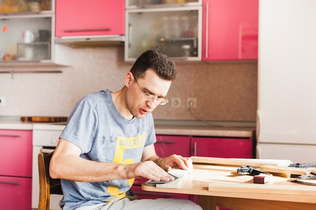 Mężczyzna w kwarantannie w domu wykonuje drewniane elementy dekoracyjne do domu,