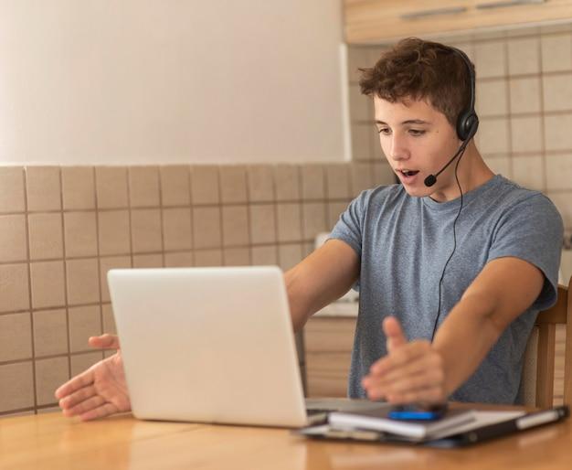 Mężczyzna w kwarantannie w kuchni przy pracy z laptopem