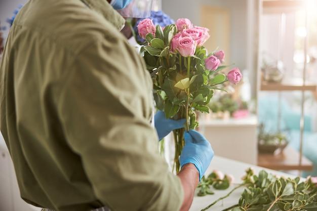 Mężczyzna w lateksowych rękawiczkach robi bukiety świeżych kwiatów podczas dnia pracy w kwiaciarni
