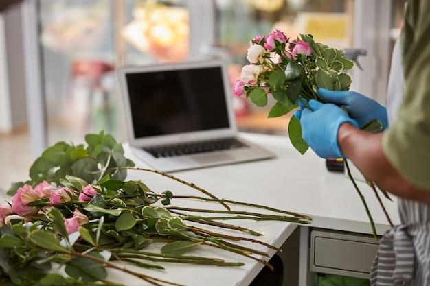 Mężczyzna w lateksowych rękawiczkach robi zamówienie online na laptopie i robi bukiet róż