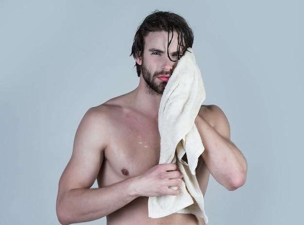 Mężczyzna w łazience z umięśnionym ciałem na szarym porannym myciu obudź się codzienne higiena seksowny facet myj spa relaks mężczyzna z mokrymi włosami trzymaj ręcznik po prysznicu