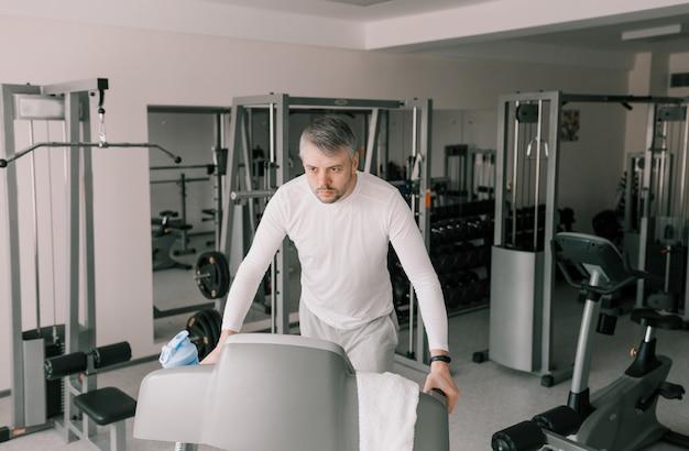 Mężczyzna w lekkim ubraniu chodzi po bieżni na siłowni. trening cardio