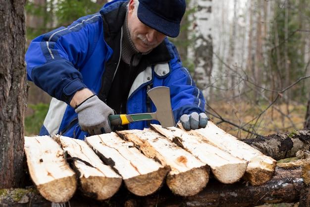 Mężczyzna w lesie pracuje siekierą robiąc stół obozowy narzędzia turystyka styl życia