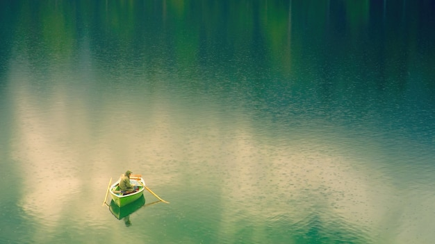 Mężczyzna w łodzi na jeziorze w ciągu dnia