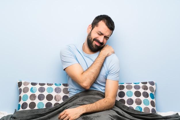 Mężczyzna w łóżku cierpiący na ból ramienia za to, że podjął wysiłek