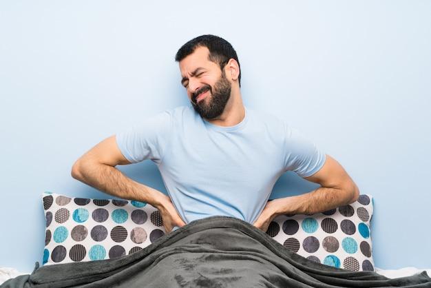 Mężczyzna w łóżku cierpiący na bóle pleców za to, że podjął wysiłek